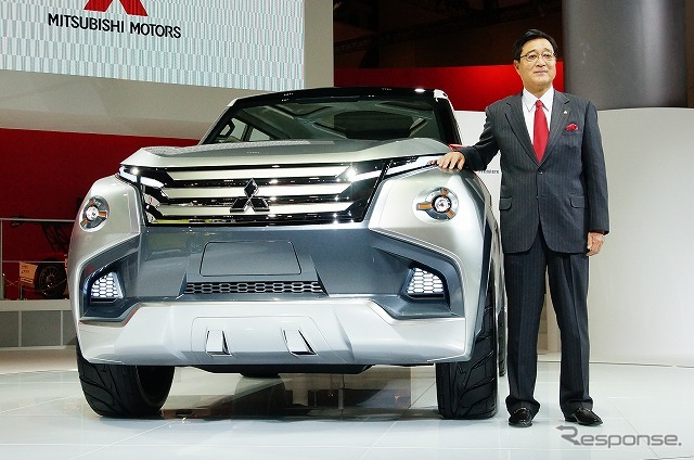 President Osamu Masuko stands beside the concept GC-PHEV