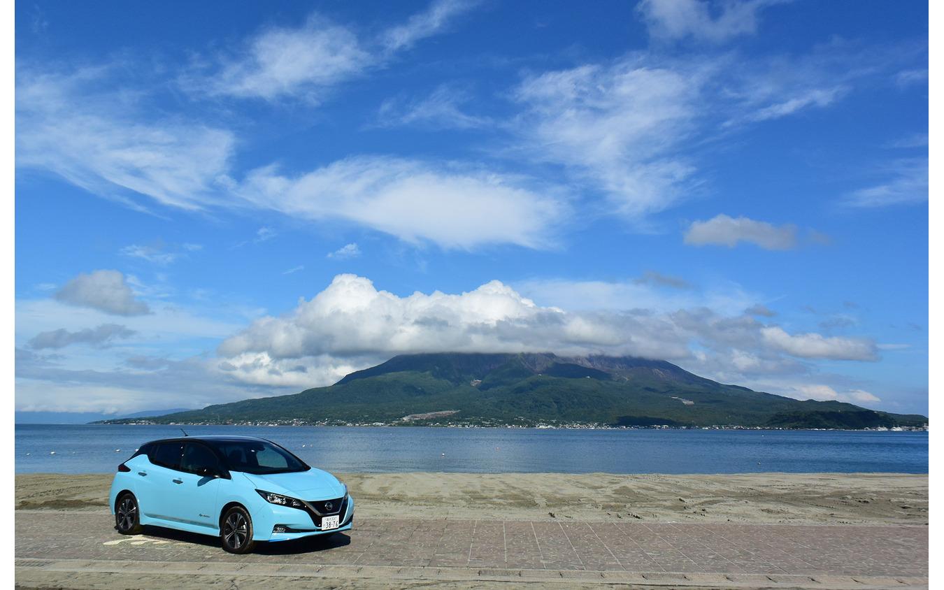 桜島をバックに記念撮影。背後の浜は海水浴場。