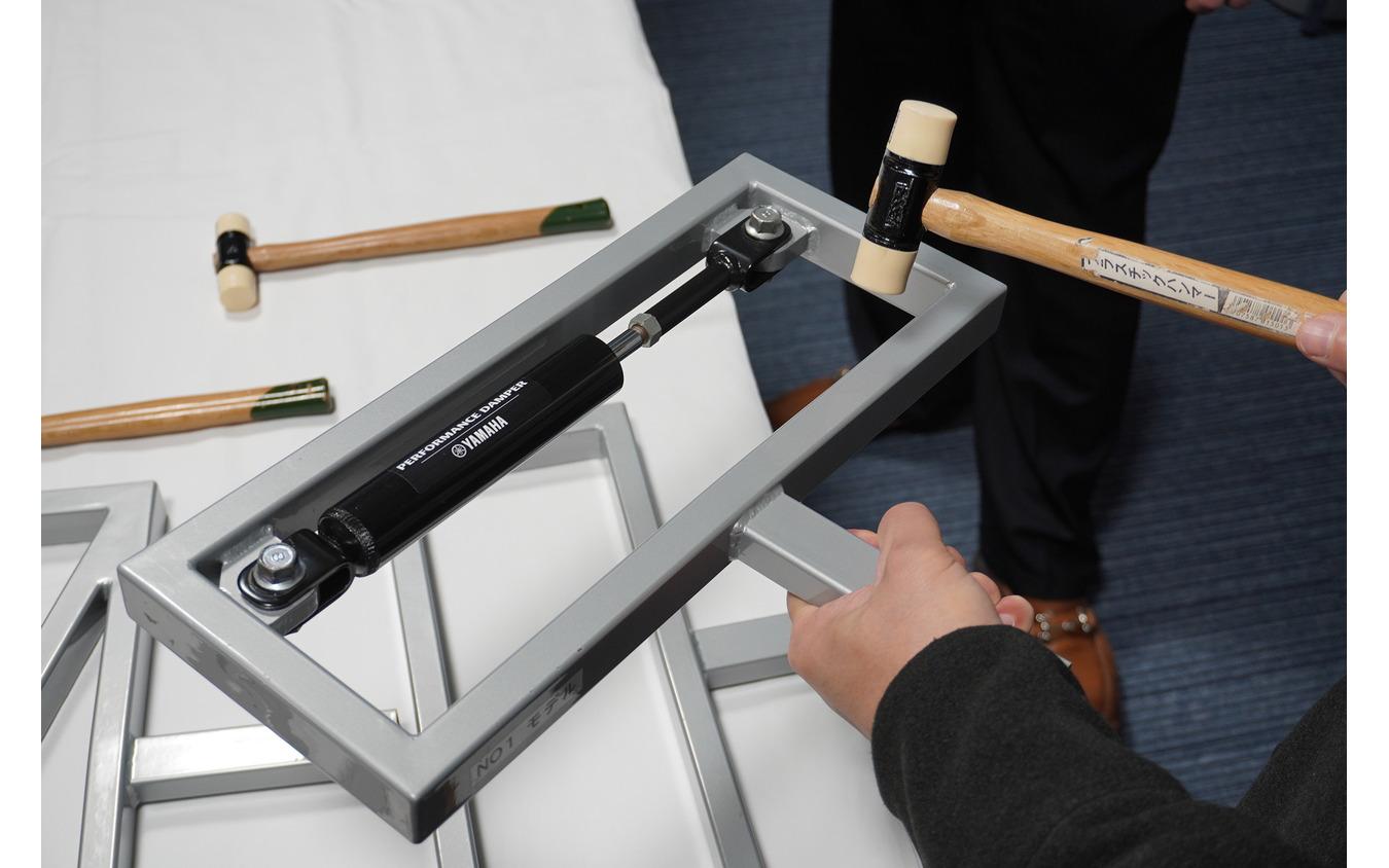 振動の減衰を確かめるためのデモ用機材。パフォーマンスダンパー を装着したものは、手に伝わる振動がまったくなくなる。