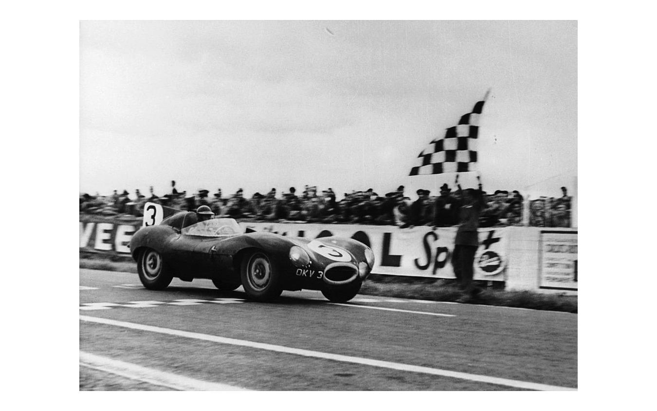 ランス12時間耐久でチェッカーを受けるジャガーDタイプ(1954年)。運転席はケン・ウォートン、組んだのはピーター・ホワイトヘッド。