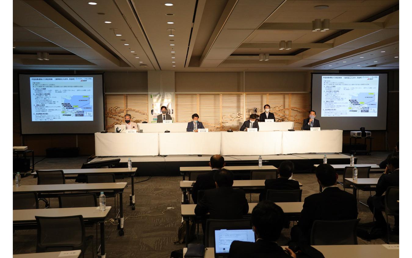 第二部のパネルディスカッションは事業者の方々。右から、西日本鉄道・日高悟氏、みちのりホールディングス・浅井康太氏、ZMP・西村明浩氏、BOLDLY・佐治友基氏、Tier IV・加藤真平氏。モデレータは、SIP-adus構成員で国際モータージャーナリストの清水和夫氏。