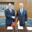 技術協力協定に署名した周局長(左)と高井専務理事(右)。