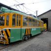 旧式の500型車両を改造した散水車が芝刈り電車を牽引する