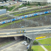 Z-class電車(Route 70)がBatman Avenue Bridgeを走る。その橋の下を中距離電車「METRO」が行く。