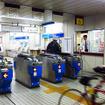 自転車を転がして千葉みなと駅の改札口を通る参加者たち(11月30日、千葉モノレール実証実験「サイクル&モノレール」)