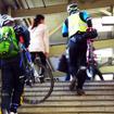 自転車を担いで階段を昇り、モノレール乗り場へと向かう参加者たち(11月30日、千葉モノレール実証実験「サイクル&モノレール」)